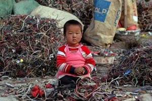Child surrounded by toxic electronic waste and scraps